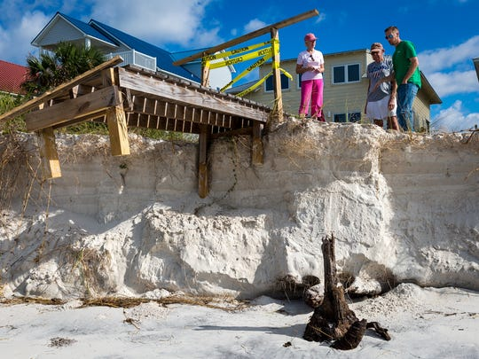 Cape San Blas, Fla. residents Linda and Buddy Gerald, left, survey the erosion damage caused to their rental property's dune walkover with maintenance man Chris Harwood, right, in October 2015. After a strong storm worsened the critical erosion in the Panhandle beach community, the Geralds found themselves needing to rebuild the walkover for a third time.
