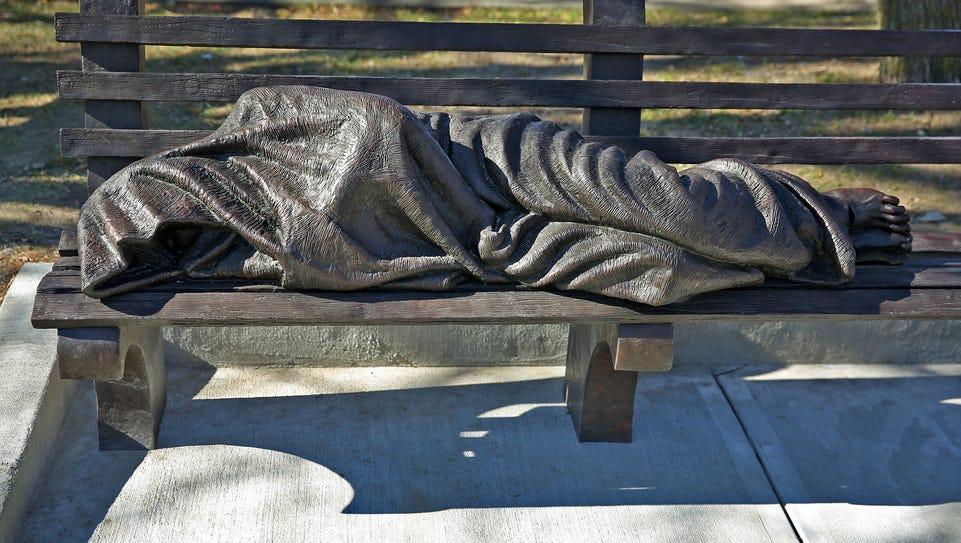 A blanketed figure on a park bench, the Homeless Jesus
