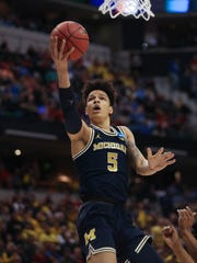 Michigan Wolverines forward D.J. Wilson scores against Louisville  during first half action Sunday, March 19, 2017 at Bankers Life Fieldhouse in  Indianapolis, Indiana.