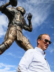 Peyton Manning poses for photos with fans in front of his statue, before the Colts' game against the San Francisco 49ers at Lucas Oil Stadium, Sunday, Oct. 8, 2017.