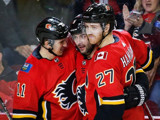 Calgary Flames' Mark Giordano, centrer, celebrates his goal with teammates Mikael Backlund, left, from Sweden, and Dougie Hamilton during first-period NHL hockey game action against the Colorado Avalanche in Calgary, Alberta, Saturday, Feb. 24, 2018. (Jeff McIntosh/The Canadian Press via AP)