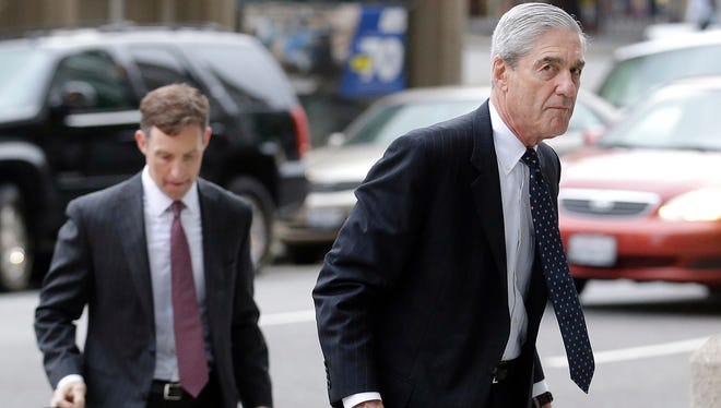 Attorney and former FBI Director Robert Mueller (right) arrives for a court hearing April 21, 2016 at the Phillip Burton Federal Building in San Francisco.