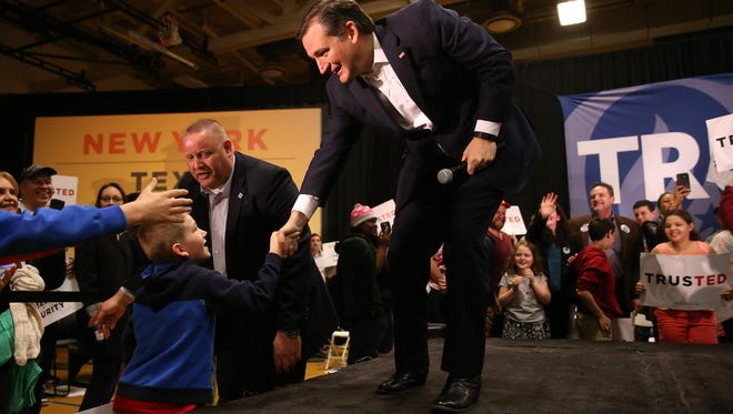 Republican presidential candidate Ted Cruz greets a young supporter during a rally at MCC.