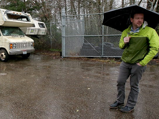Chris Piercy, program supervisor at Kitsap County Public Works Solid Waste Division, stands outside the gate of the lot of RVs ready to be scrapped.