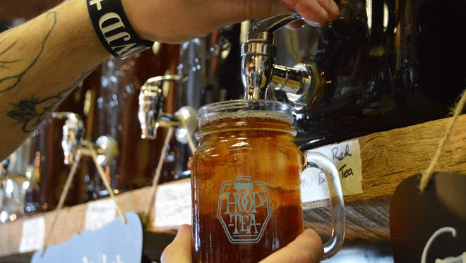 A Backshore Brewing Co. employee pours a glass of Hoop Tea for a customer. The brewery has a few tea flavors available to try before the big launch coming later this Spring.