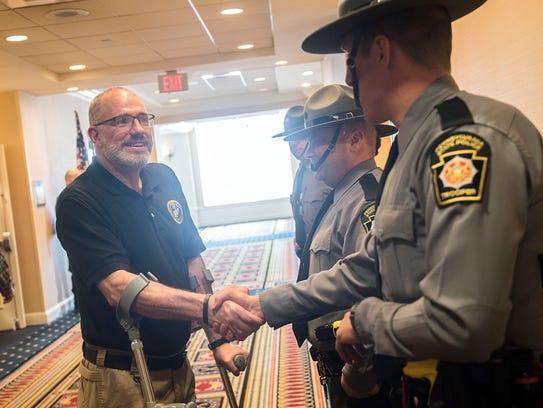 Bob Bemis, left, shakes the hand of a Pennsylvania