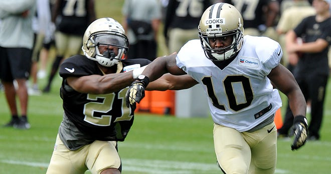 New Orleans Saints wide receiver Brandin Cooks (10) pushes off cornerback Patrick Robinson (21) during NFL football training camp in White Sulphur Springs, W. Va., Sunday, July 27, 2014. (AP Photo/Chris Tilley)