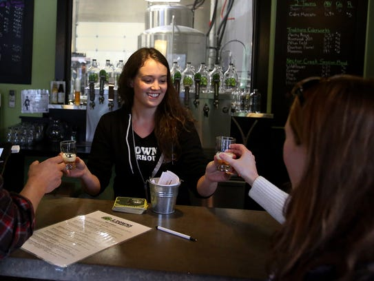 Lauren Holmes, center, serves cider to guests at the