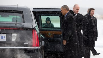 President Obama walks in the snow to his motorcade vehicle as he arrives on Air Force One at Detroit Metropolitan Wayne County Airport in Detroit, Wednesday, Jan. 20, 2016.