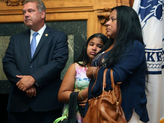 Jaelyn Rodriguez, 11, is comforted by her mother Teresa