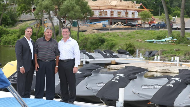 Mario Daniele, founder and president of Daniele Family Companies, with sons/vice presidents Danny, left, and Anthony at their Southpoint Marina on Irondequoit Bay in Penfield Friday. Behind them, construction is underway on their new boat club development.