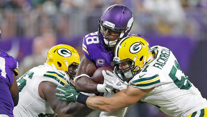 Green Bay Packers outside linebacker Kyler Fackrell (51) and defensive end Mike Daniels (76) converge on running back Adrian Peterson (28) against the Minnesota Vikings at U.S. Bank Stadium.