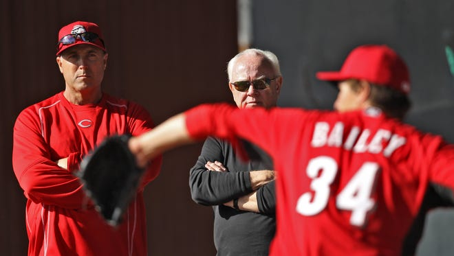 Reds manager Bryan Price, left, and general manager Walt Jocketty, center, observe starting pitcher Homer Bailey, right, throw during a bullpen session at spring training, Friday, Feb. 27.