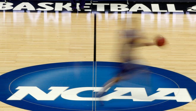 A player runs across the NCAA logo at midcourt during practice in Pittsburgh before an NCAA tournament college basketball game.
