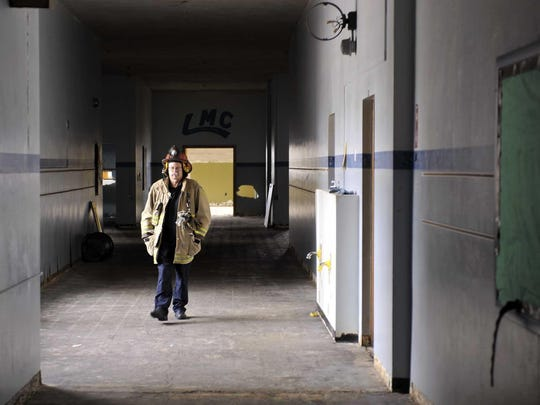 Fort Dodge Fire Department Capt. Paul Neeson walks down the hallway in the old Duncombe Elementary School building.
