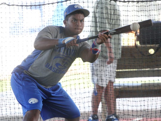 Giovanny Lorenzo, of Canterbury's varsity baseball team, works on bunting during practice at FGCU on Tuesday.