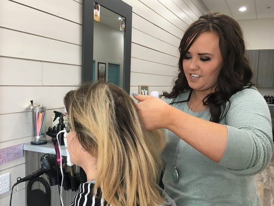 Macy Pirlet, owner of Dragonfly Salon, works on a customer's