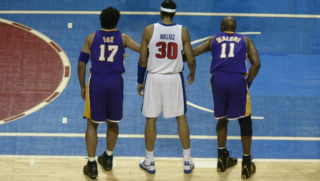 Detroit Pistons forward Rasheed Wallace, center, is flanked by Rick Fox, left, and Karl Malone during Game 4 of the NBA Finals on June 13, 2004, at the Palace of Auburn Hills.