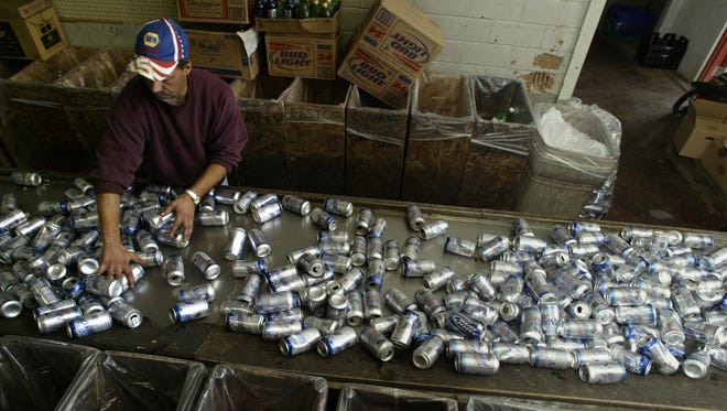 An employee at B & L's Too in Fort Dodge sorts cans brought to the center for redemption.