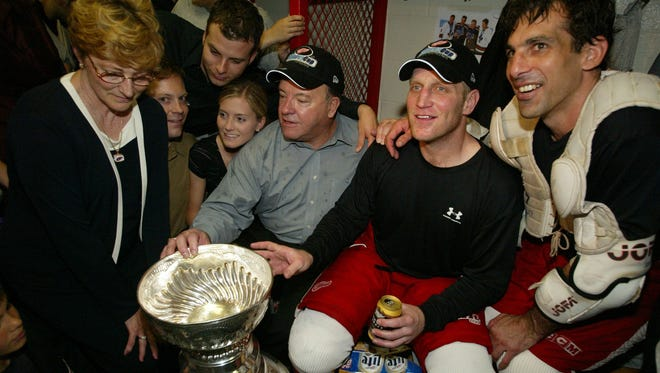 Scotty Bowman, Brett Hull and Chris Chelios in the locker room with the 2002 Stanley Cup.