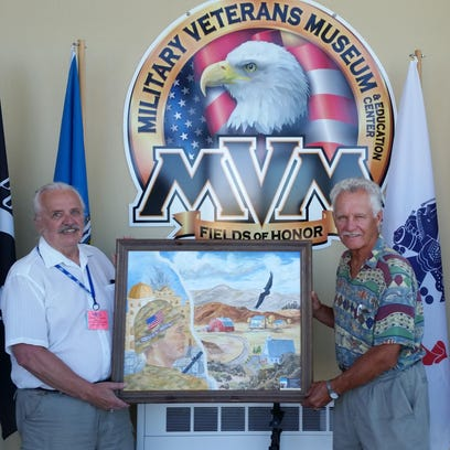 "Military Veterans Museum volunteer Raymond Lorel Ellingsen Jr., left, and painter Jerry Kuiper hold Kuiper's oil painting, ""Why I Serve,"" which is on temporary display at the museum."