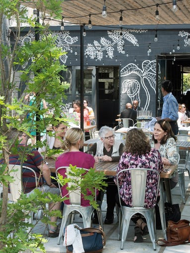 Diners enjoy a meal on Selden Standard's shady patio.