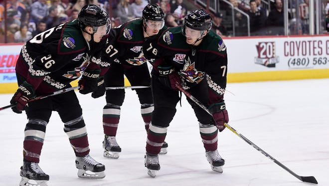 Nov 25, 2016; Glendale, AZ, USA;  Coyotes center Laurent Dauphin (76) and defenseman Michael Stone (26) and left wing Lawson Crouse (67) line up for a faceoff in the third period against the Oilers at Gila River Arena.