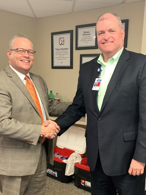 JJ Hodshire (left), vice president and chief operating officer, shakes hands with retiring CEO Duke Anderson (right) on Friday, May 29, Anderson's last day in the role. Hodshire succeeds Anderson as president and CEO effective June 1.