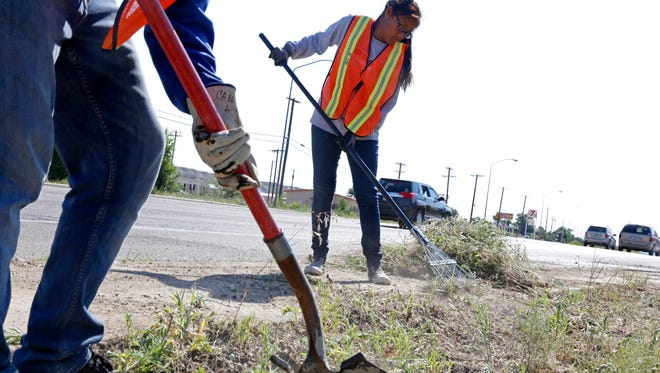 Sapphire Williams, 14, of Shiprock, cleans up the roadside June 25 along U.S. Highway 64 east of the Shiprock Chapter house as part of the Navajo Nation's summer youth employment program.