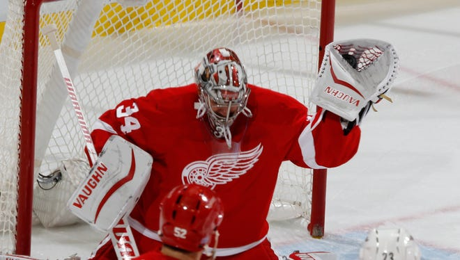 Red Wings goalie Petr Mrazek gloves a high shot in the second period of Tuesday's loss to the Hurricanes.