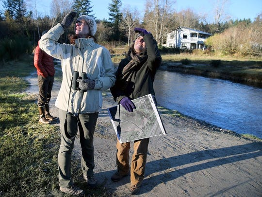 Deborah Jensen, of Seattle, and Sandra Staples-Bortner, of Belfair, watch eagles during the Puget Sound Partnership's Wednesday tour of Chico Creek.
