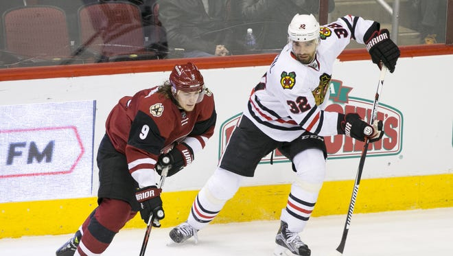 Coyotes' Viktor Tikhonov controls the puck as the  Blackhawks Michal Rozsival defends during the first period of the NHL game at Gila River Arena in Glendale on Tuesday, December 29, 2015.