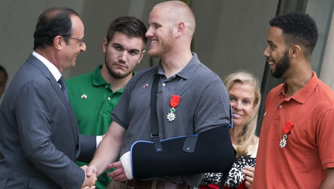 French President Francois Hollande shakes hands with Spencer Stone. Stone, Alek Skarlatos, second from left and Anthony Sadler, right, along with U.S. ambassador to France Jane Hartley, attend a reception at the Elysee Palace in Paris on Aug. 24, 2015.