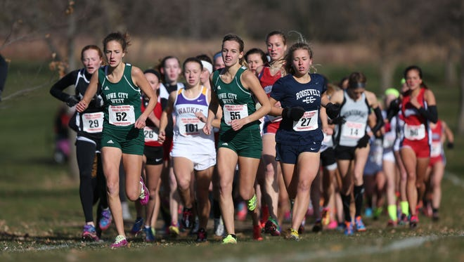 "West High runners Bailey Nock (52) and Emmie Skopec (55) lead the pack alongside eventual 4-A champion Megan Schott of Des Moines Roosevelt during the Iowa High School state cross country meet on Nov. 1, 2014. West High coach Mike Parker is excited about the move to 5,000 meters. ""I know the girls here in Iowa City, whether we are talking about City High, Regina or West High, have no fear of running 800 meters further,"" Parker said. ""They are more than capable of doing it so I just think this is something that is going to grow our sport and that is why I have been fighting for this for years."""