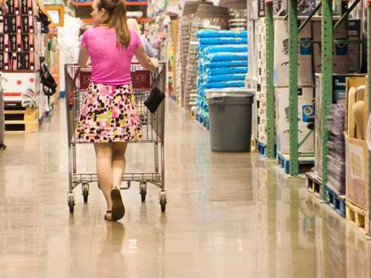 A woman pushing a cart down the aisle of a warehouse
