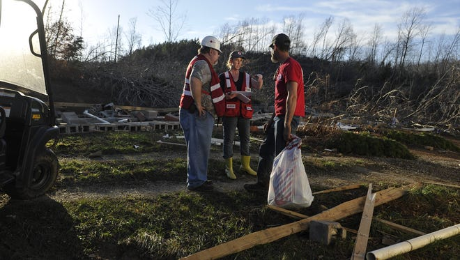Pictured, from left, Red Cross volunteers Edward England and Michelle Balsley, both of White Bluff, talk with Tony Goodwin at his home in Perry County two years ago following a tornado