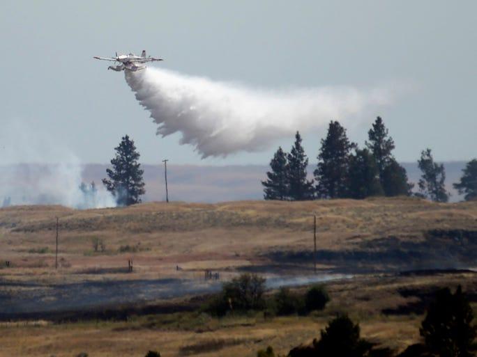 A firefighting aircraft drops water near Fishtrap Lake on July 20 near Cheney, Wash.