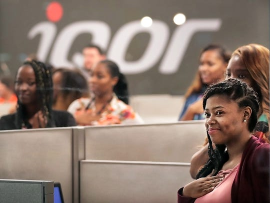 New IQor employees in the customer support call center watch as IQor executives mark an expansion of the company's  southeast Memphis facility.