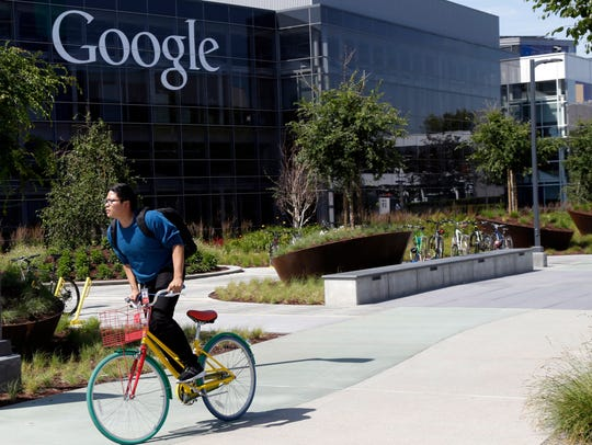 A worker rides a bike on Google's campus in Mountain