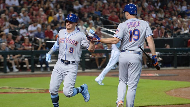 New York Mets center fielder Brandon Nimmo (9) slaps hands with New York Mets right fielder Jay Bruce (19) after scoring a run against the Arizona Diamondbacks during the first inning at Chase Field.