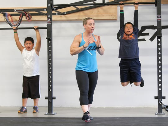Holly Cohen Mata leads kids in their Crossfit class Monday. ""