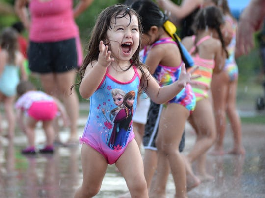 Kataleya Soto, 2, screams as she runs through the splash