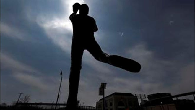 A statue outside the Joliet Slammers minor league baseball team's stadium, stands in silhouette Monday, April 6, 2020, in Joliet, Ill.