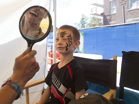 Garrett Belarde, 8, checks out his painted face at