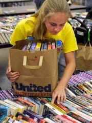 Ronald W. Erdrich/Reporter-NewsMakayla Gothard helps her sister search for books during Sunday's Friends of the Library Book Sale at the Abilene Civic Center June 21, 2015. Sunday shoppers crammed as many books as they could in a paper bag, paying $6 for each full bag they carried out.