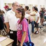 In-coming seventh-grader Hannah Davis, center, waits with her father, Ken Davis, as she collects her school schedule.