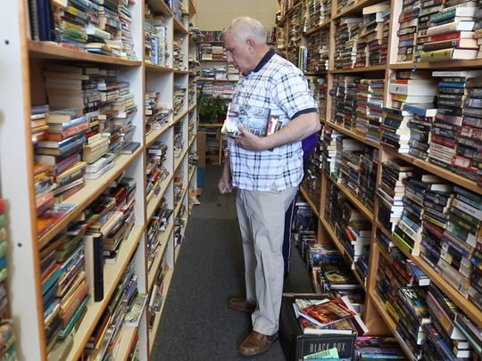Steve Epstein, owner of Bookends in Henrietta, helps a customer find specific authors.