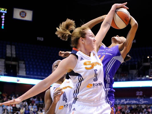Connecticut Sun's Kelsey Griffin (5) blocks the shot of Phoenix Mercury's DeWanna Bonner (24) as Connecticut Sun's Danielle McCray (4) looks on during the first half of their WNBA basketball game in Uncasville, Conn., Thursday, June 12, 2014. (AP Photo/Fred Beckham)