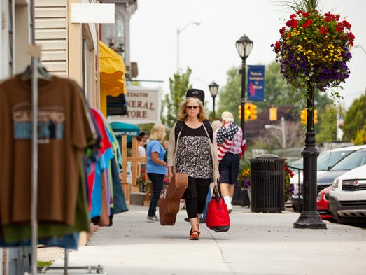 Jan Krist, a folk singer-songwriter from Detroit, walks down the sidewalk on Huron Avenue as she heads for performance during Thumbfest August 30, 2014 in Lexington. The music festival featured 54 performers on 11 stages.