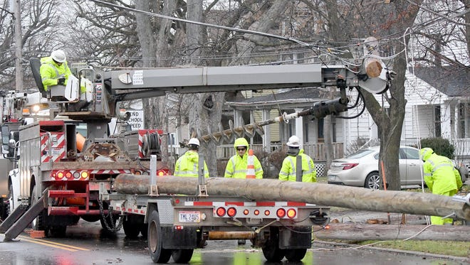 Ohio Edison workers repair a utility pole in the 400 block of South Main Street after an automobile accident early Tuesday morning.